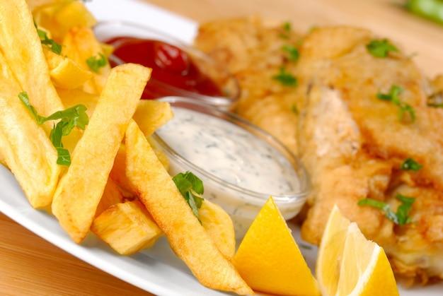 Weißer teller mit fisch, pommes, mayo, ketchup und zitrone