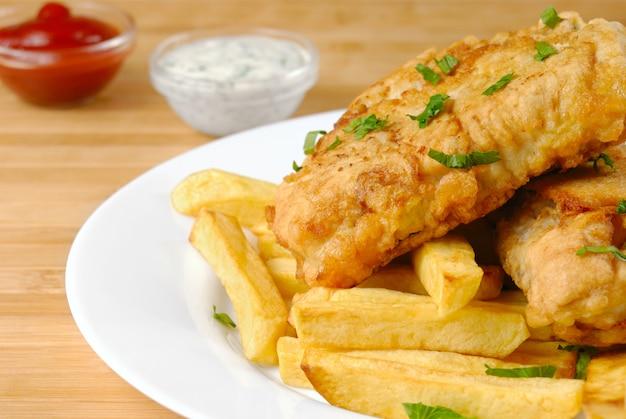 Weißer teller mit fish and chips, mayo und ketchup