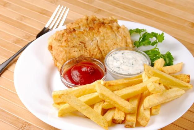 Weißer teller mit fish and chips, mayo, zitrone und ketchup