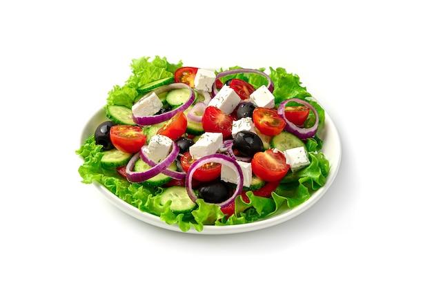 Weißer teller mit frischem griechischem salat lokalisiert auf einem weißen hintergrund. seitenansicht, nahaufnahme.