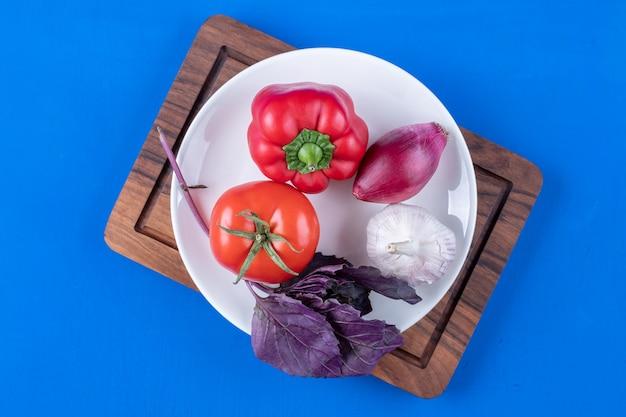Weißer teller mit frischem reifem gemüse auf holzbrett.