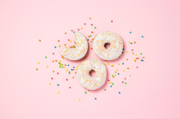 Weißer teller mit frischen leckeren süßen donuts auf einem rosa hintergrund. bäckereikonzept, frisches gebäck, leckeres frühstück, fast food, café. flache lage, draufsicht