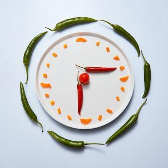 Weißer teller mit gefütterten paprika-scheiben und kirschtomaten in form einer uhr. konzept des kochens oder zeit zum essen