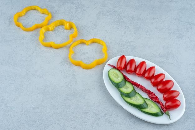 Weißer teller mit gehackter gurke, tomatenkirsche und pfeffer. hochwertiges foto