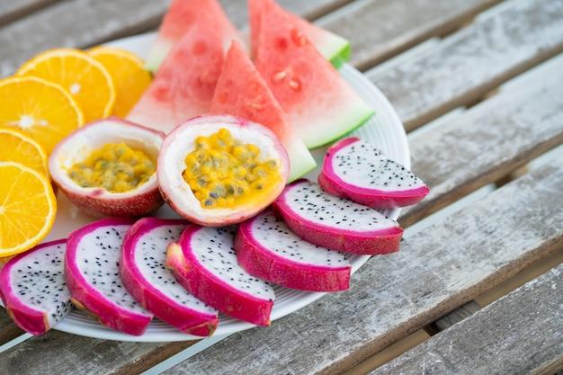 Weißer teller mit geschnittenen früchten. frisches obst und vitamine. stillleben gefärbte sommerfrüchte.