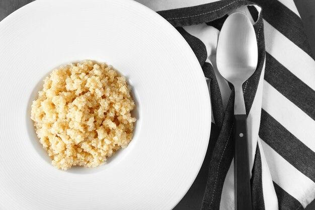 Weißer teller mit gesundem quinoa-porridge auf dem tisch