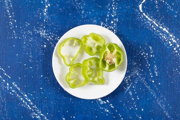 Weißer teller mit grünen paprikaringen auf marmoroberfläche.