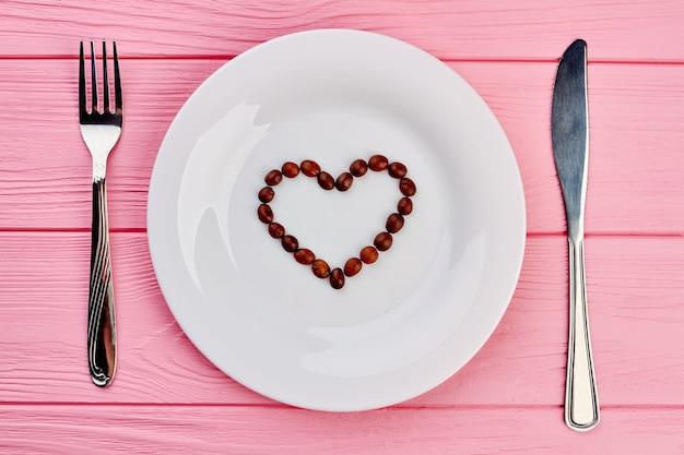 Weißer teller mit herz aus kaffeebohnen. weißer teller mit herzförmigen kaffeebohnen, gabel und messer auf rosa hölzernem hintergrund, draufsicht.