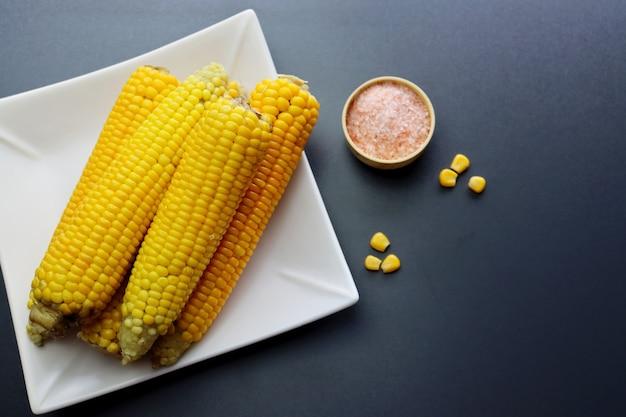 Weißer teller mit köstlichen gekochten maiskolben und rosa salz auf einem hellgrauen tisch, draufsicht.