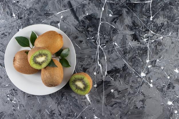 Weißer teller mit köstlichen kiwis auf marmoroberfläche