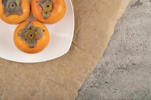 Weißer teller mit köstlichen reifen fuyu-kakis auf marmoroberfläche