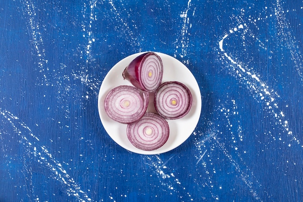 Weißer teller mit lila zwiebelringen auf marmoroberfläche