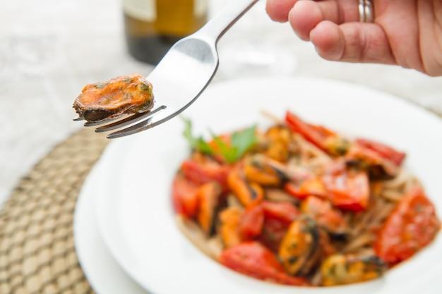 Weißer teller mit teigwarenspaghettis, -muschel und -tomaten