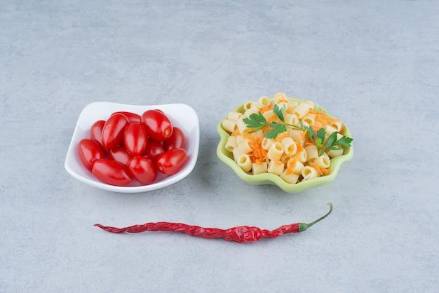 Weißer teller mit tomatenkirsche und grüner teller mit köstlichen makkaroni