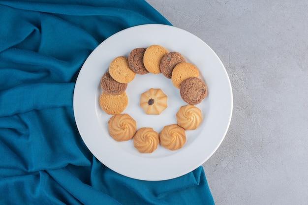 Weißer teller mit verschiedenen süßen keksen auf steinhintergrund.