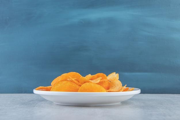 Weißer teller mit würzigen chips auf stein gelegt.