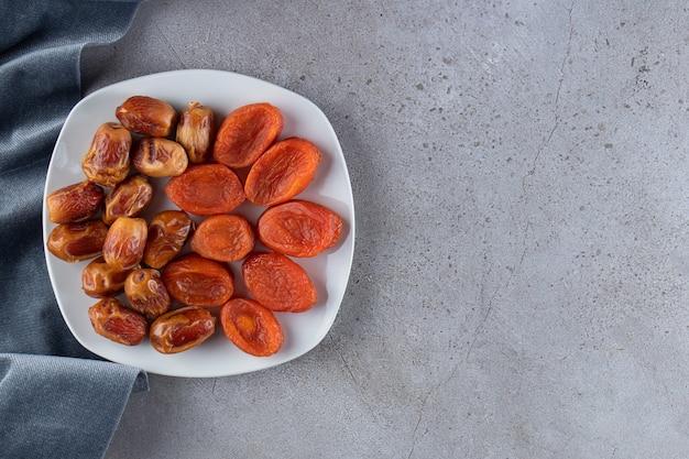 Weißer teller voller getrockneter datteln und aprikosen auf steinoberfläche