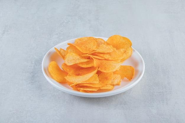 Weißer teller voller würziger chips auf stein gelegt.