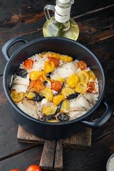 Weißer tilapia-fisch mit basmatireis und kirschtomaten auf dunklem holztisch