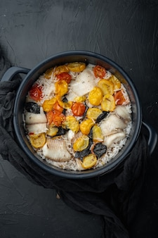 Weißer tilapia-fisch mit basmatireis und kirschtomaten, auf schwarzem tisch, draufsicht