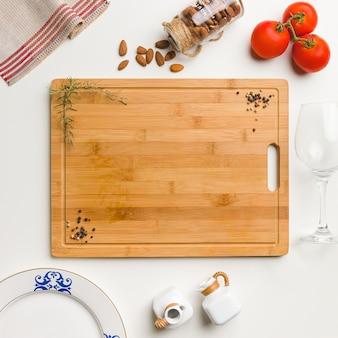 Weißer tisch, hölzernes schneidebrett mit platz für text, zutaten und utensilien
