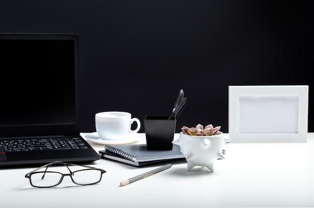 Weißer tisch mit laptop, kaffeegläsern für fernarbeit oder studium. schwarzer laptop mit leerer display-layout-vorlage auf schwarzem hintergrund. büro-pc-schreibtischarbeitsplatz im innenministerium mit kopienraum.