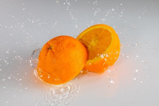 Weißer tisch und eine dünne wasserschicht. zwei hälften reifer orange und viele spritzer