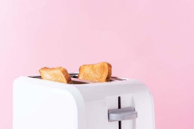 Weißer toaster mit gebratenem toastbrot auf rosa hintergrund, abschluss oben