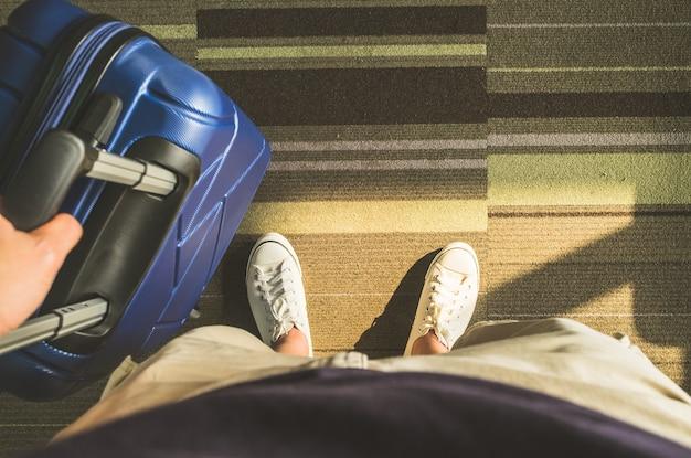 Weißer turnschuh und reisekoffer mit morgensonnenlicht am flughafenterminal