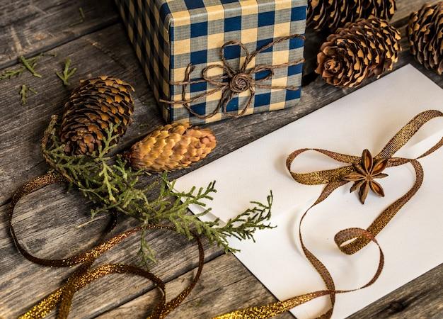Weißer umschlag auf holzwand mit tannenzapfen und weihnachtsgeschenk
