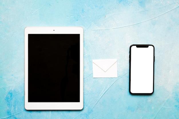 Weißer umschlag der mitteilungsikonen mit digitaler tablette und mobiltelefon auf gemaltem blauem hintergrund