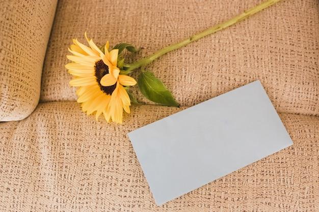 Weißer umschlag mit platz zum schreiben und eine sonnenblume