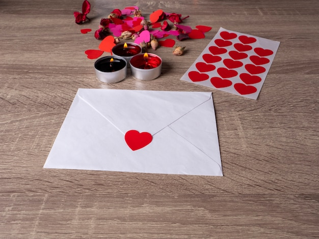 Weißer umschlag neben kerzen mit roten rosenblättern und herzen auf dem tisch