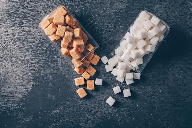 Weißer und brauner zucker in wassergläsern flach liegen