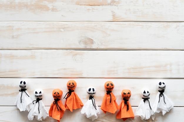 Weißer und orange papiergeist auf weißem hölzernem hintergrund, halloween-konzept.