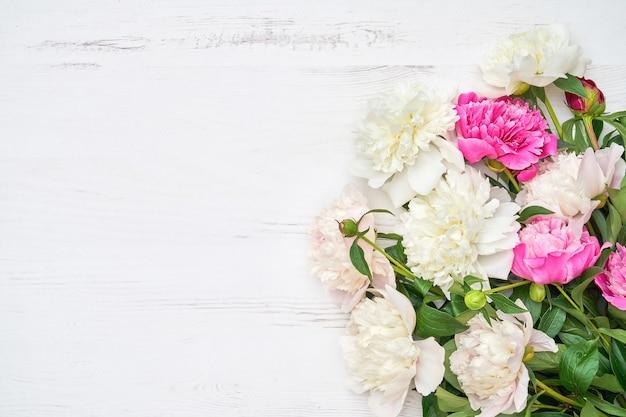 Weißer und rosa pfingstrosenstrauß auf weißem hölzernem hintergrund. speicherplatz kopieren, draufsicht. muttertag, valentinstag, geburtstagskonzept. grußkarte.