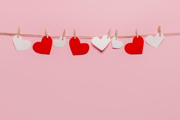 Weißer und roter herzstift auf einem seil auf lokalisiertem rosa hintergrund, liebe und valentinsgrußkonzept
