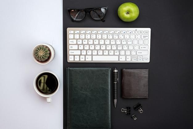Weißer und schwarzer schreibtisch mit einem kaktus, einer tasse kaffee und einem briefpapier