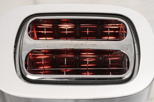 Weißer und silberner toaster auf einem weißen holztisch mit glühenden spiralen darauf