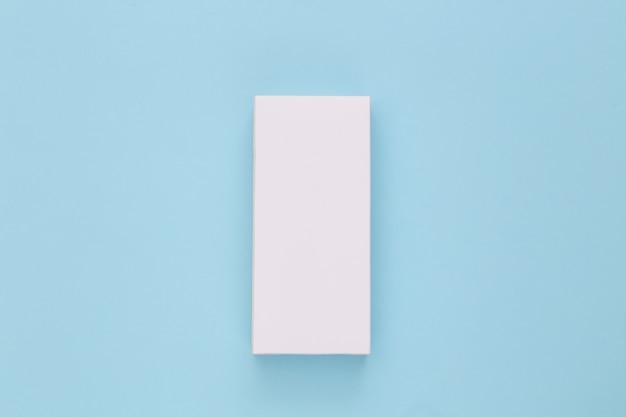 Weißer verpackungskarton auf blau. minimalismus