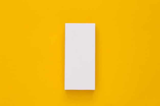 Weißer verpackungskarton auf gelb. minimalismus