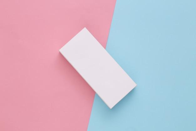 Weißer verpackungskarton auf rosa-blauem pastell. minimalismus draufsicht
