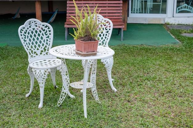 Weißer vintage-tisch und stühle mit farnpflanze in vase auf rasenhinterhof