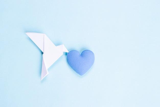 Weißer vogel gemacht vom papier, das blaues herz trägt. internationaler tag des friedens.