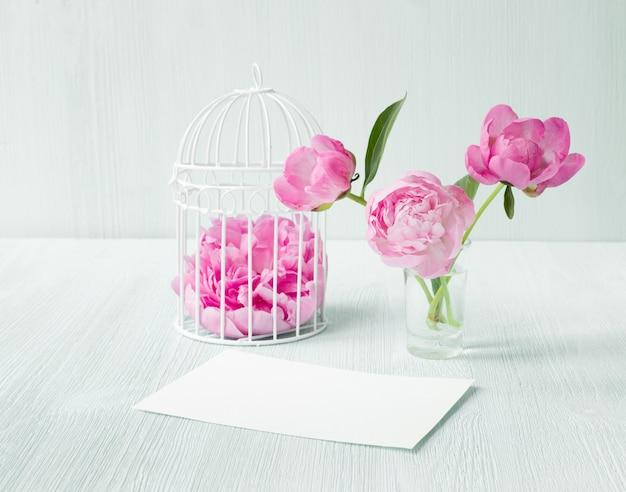 Weißer vogelkäfig mit blütenblättern auf holztisch. drei pfingstrosenblüten in glasvase. leere einladungskarte für hochzeitsfeier.