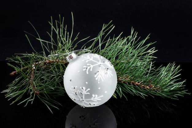Weißer vorzüglicher ball auf weihnachtsbaumzweig auf schwarzem hintergrund