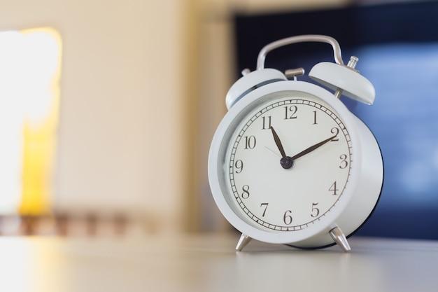 Weißer wecker analog mit glocke auf dem tisch morgens im haus. ausrüstung schnell schläfrig aufwachen.