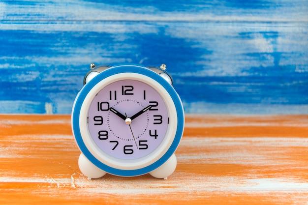 Weißer wecker auf einem orange holztisch auf blauem wandhintergrund