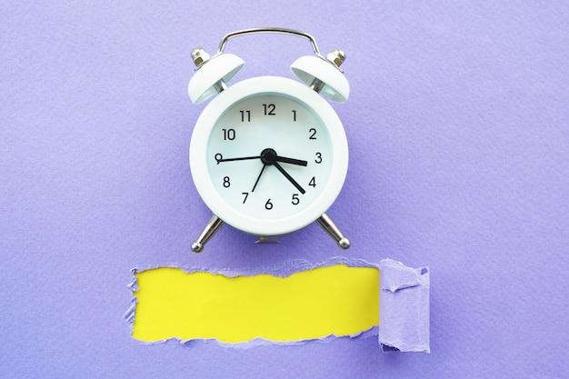 Weißer wecker auf violettem papier mit einem heftigen loch und einem gelben hintergrund. platz für text.