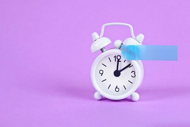 Weißer wecker auf violettem pastell